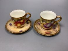 A pair of Royal Worcester fruit painted coffee cups and saucers, signed Freeman, (one saucer