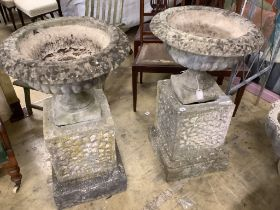 A pair of reconstituted stone urns on plinths, diameter 58cm, height 94cm