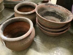 A pair of terracotta pots and three other terracotta pots, largest