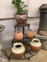 Five assorted terracotta pots together with a wrought iron corner pot stand, height 75cm