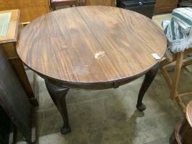 A 1920's circular mahogany extending dining table with three leaves and handle, length approx.