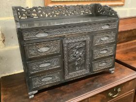 An Edwardian chinoiserie inspired ebonised oak table top cabinet, with cupboard and seven drawers,