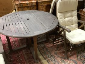 A set of four Alexander Rose stained teak folding garden chairs and matching table, diameter 120cm