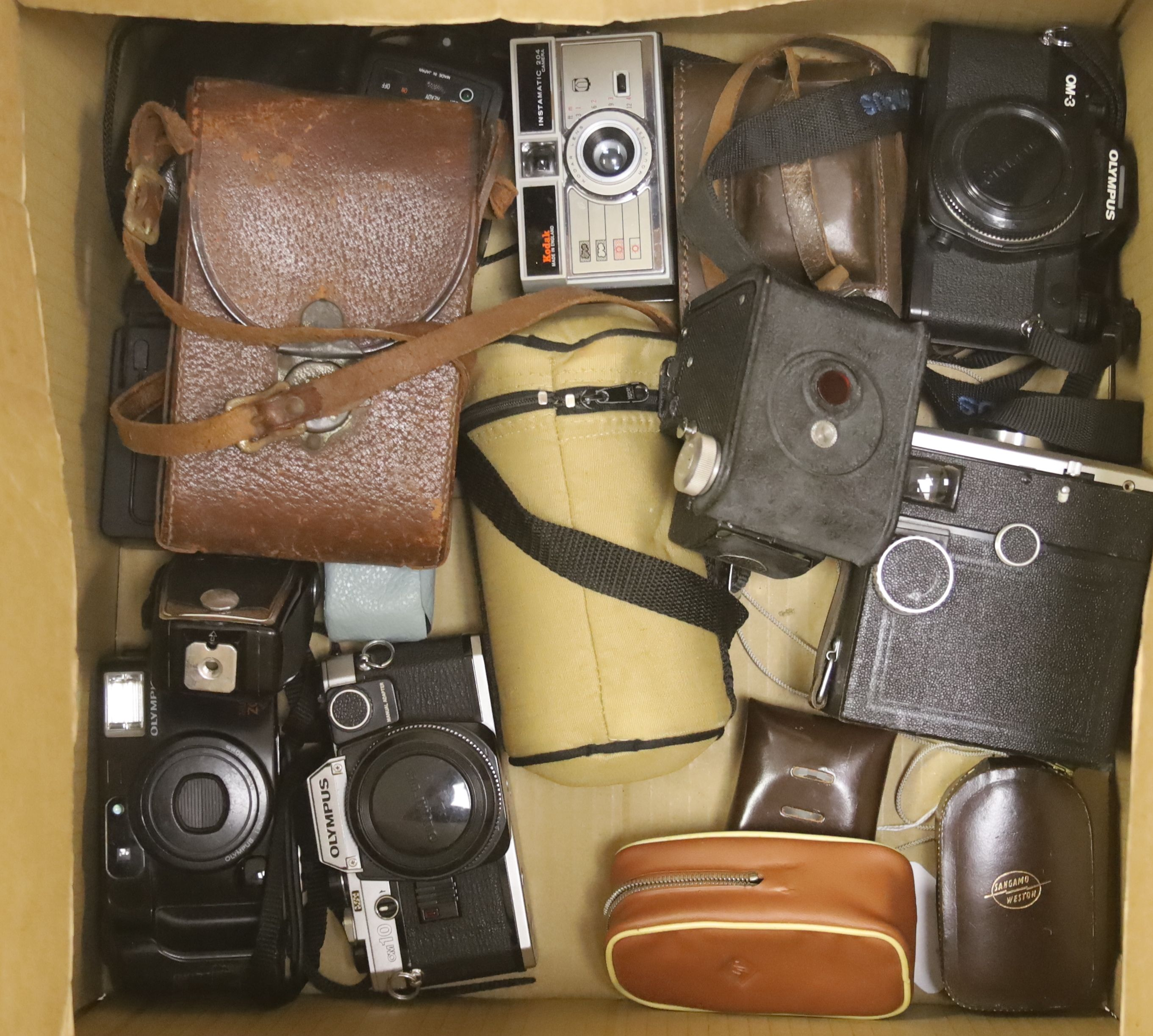 A quantity of cameras and lenses including Olympus