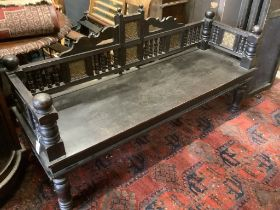 A Victorian Aesthetic period ebonised hall seat, the raised back with embossed glass inset panels,