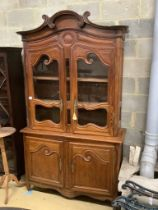 A 19th century French stained pine vitrine, with two glazed doors over panelled doors, width 133cm