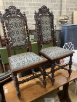 A pair of late 19th century Flemish carved oak panel backed dining chairs