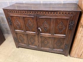 A 17th century carved and panelled oak cupboardenclosed by a pair of doors, length 139cm, depth