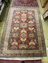 A Caucasian design red ground carpet, 310 x 228cm