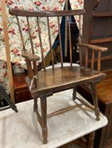 An early 19th century, possibly Welsh ash and fruitwood primitive Windsor comb back elbow chair,