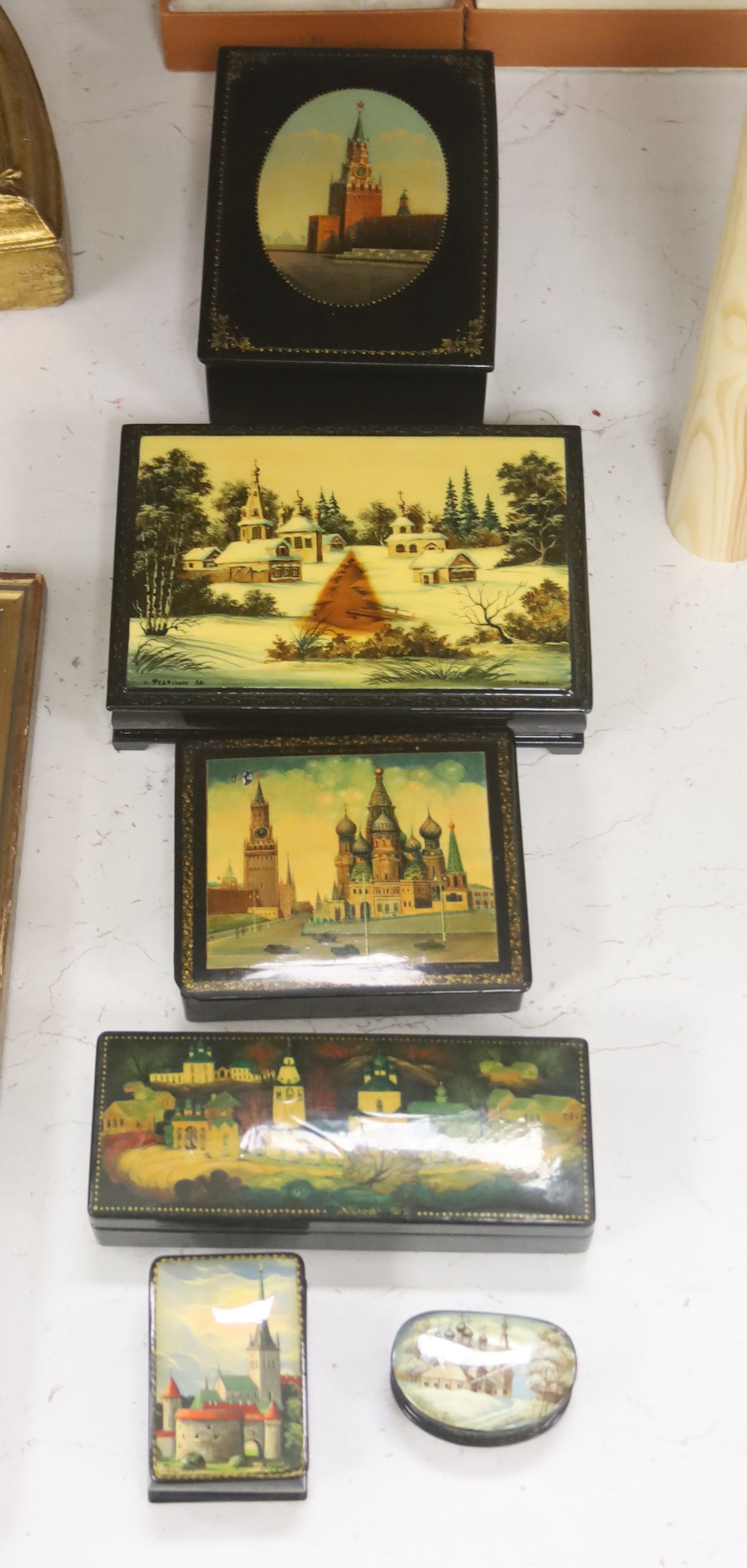 Six Russian Papier mache boxes, each decorated with churches or cathedrals, largest 17 cm