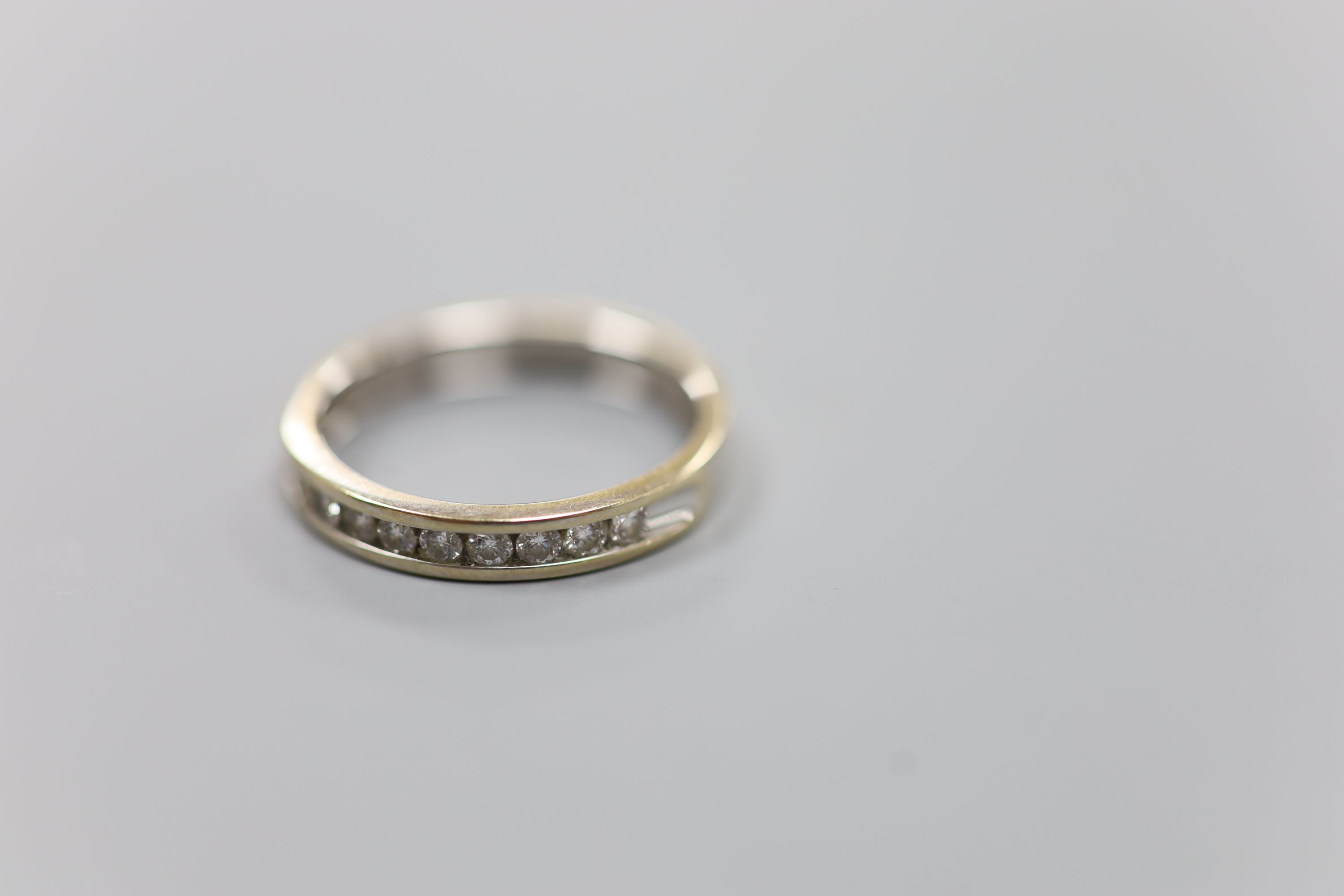 A modern 18ct white gold (worn) and nine stone channel set diamond half eternity ring, size P,gross - Image 3 of 4