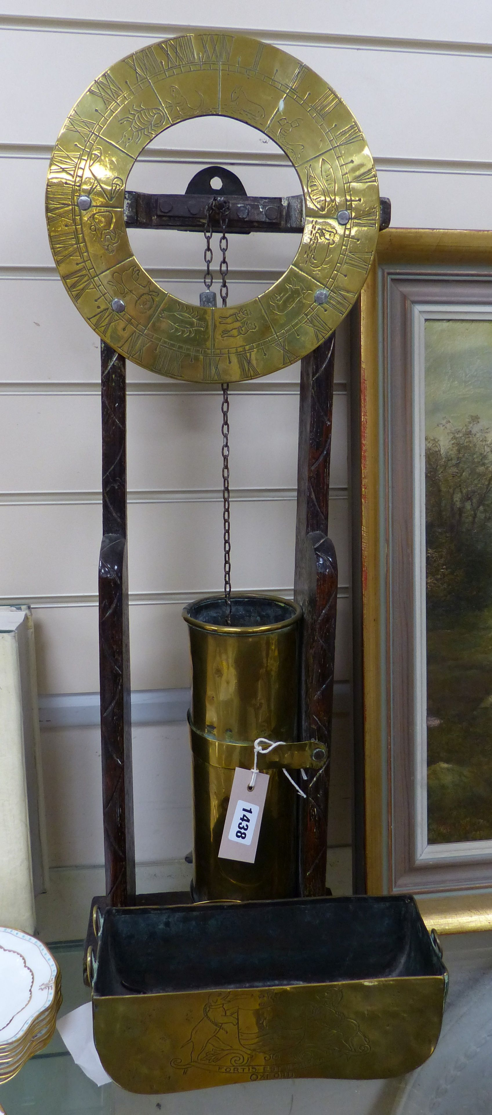 A 17th century style oak and brass 'Clepsydra' or water clock,having engraved chapter ring, water