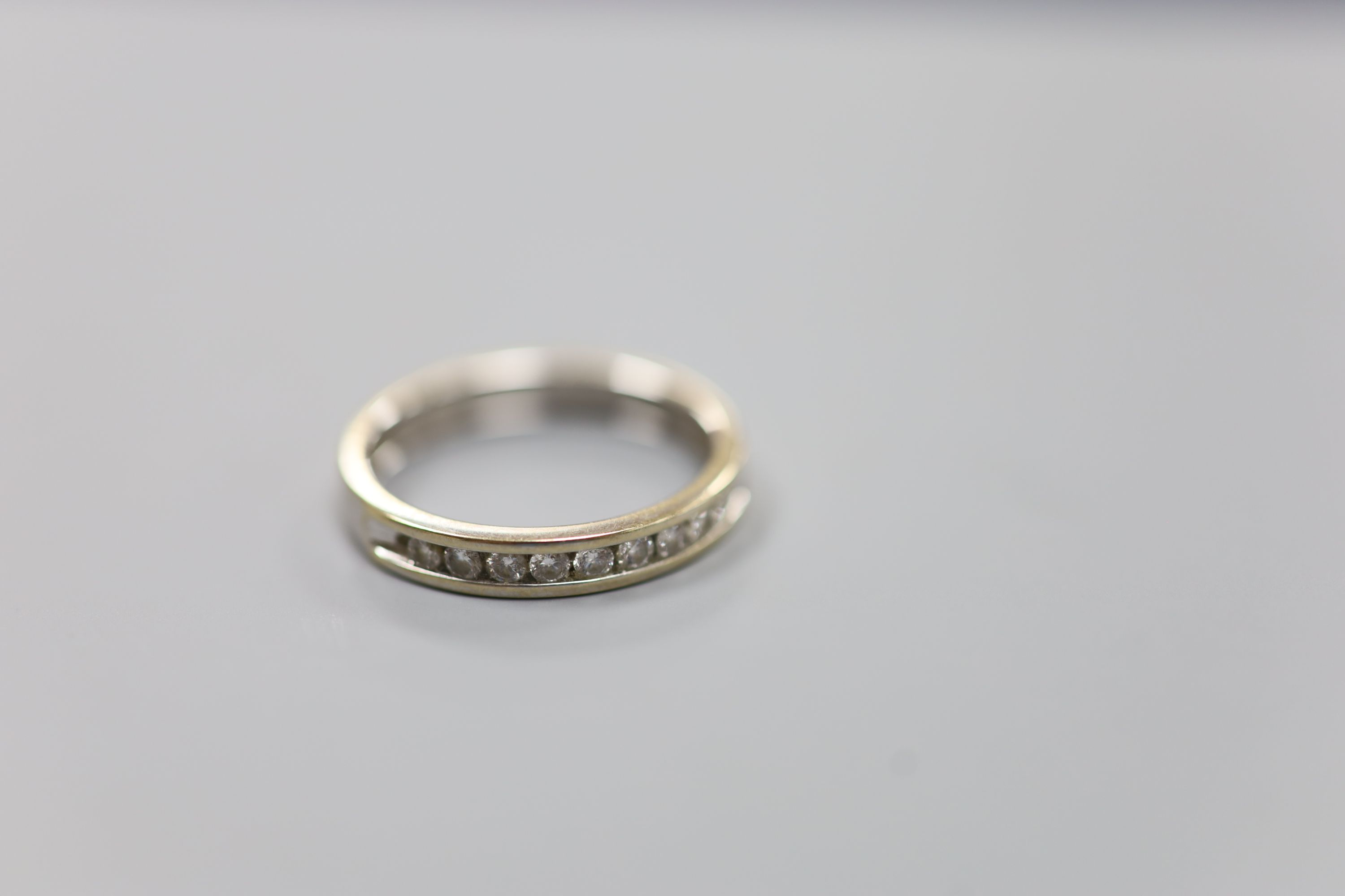 A modern 18ct white gold (worn) and nine stone channel set diamond half eternity ring, size P,gross - Image 2 of 4