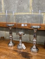 Set of three nickel plated candle stands with glass shades, height 51cm