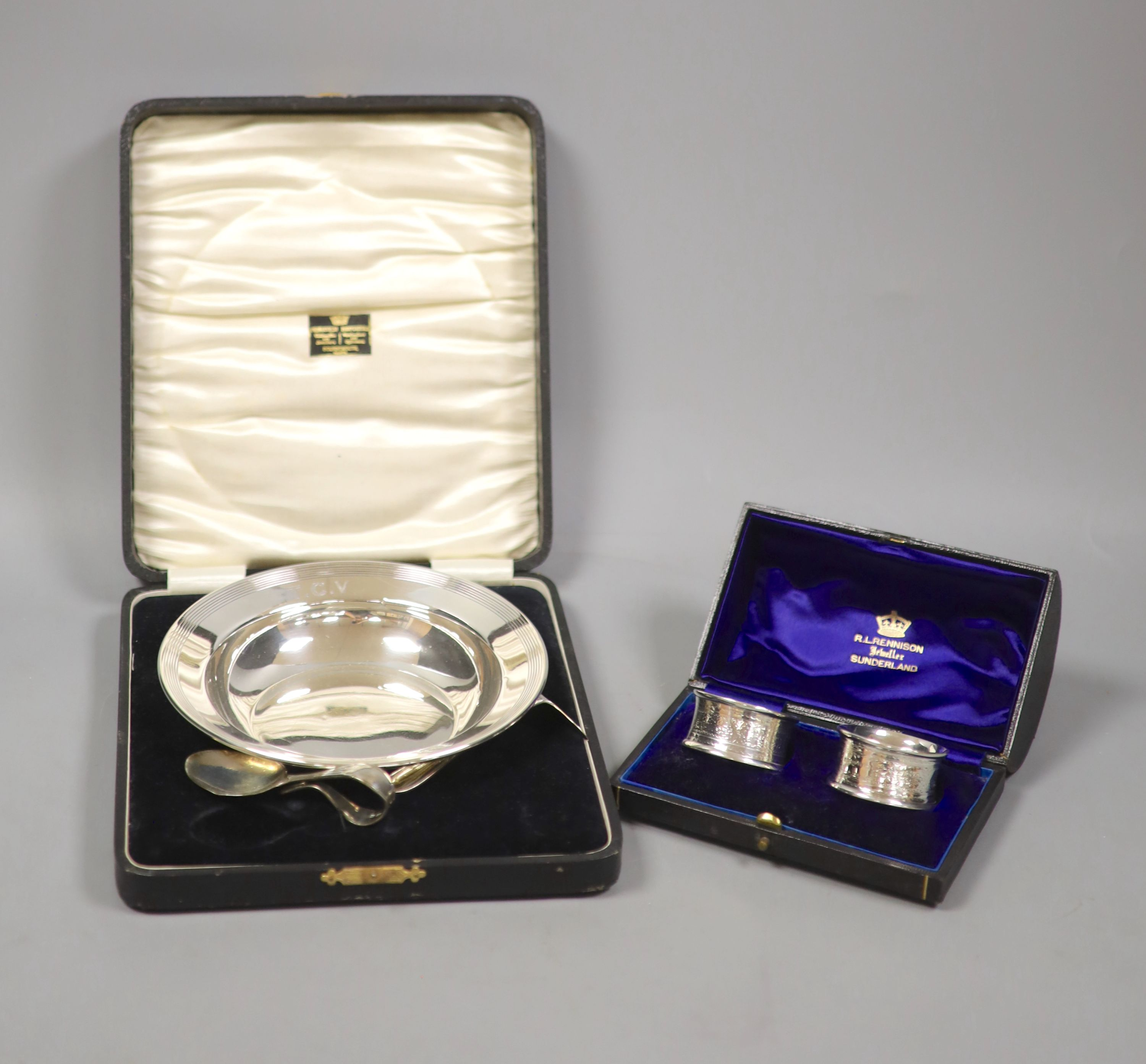 A cased christening dish with associated pusher and spoon, together with a cased pair of silver