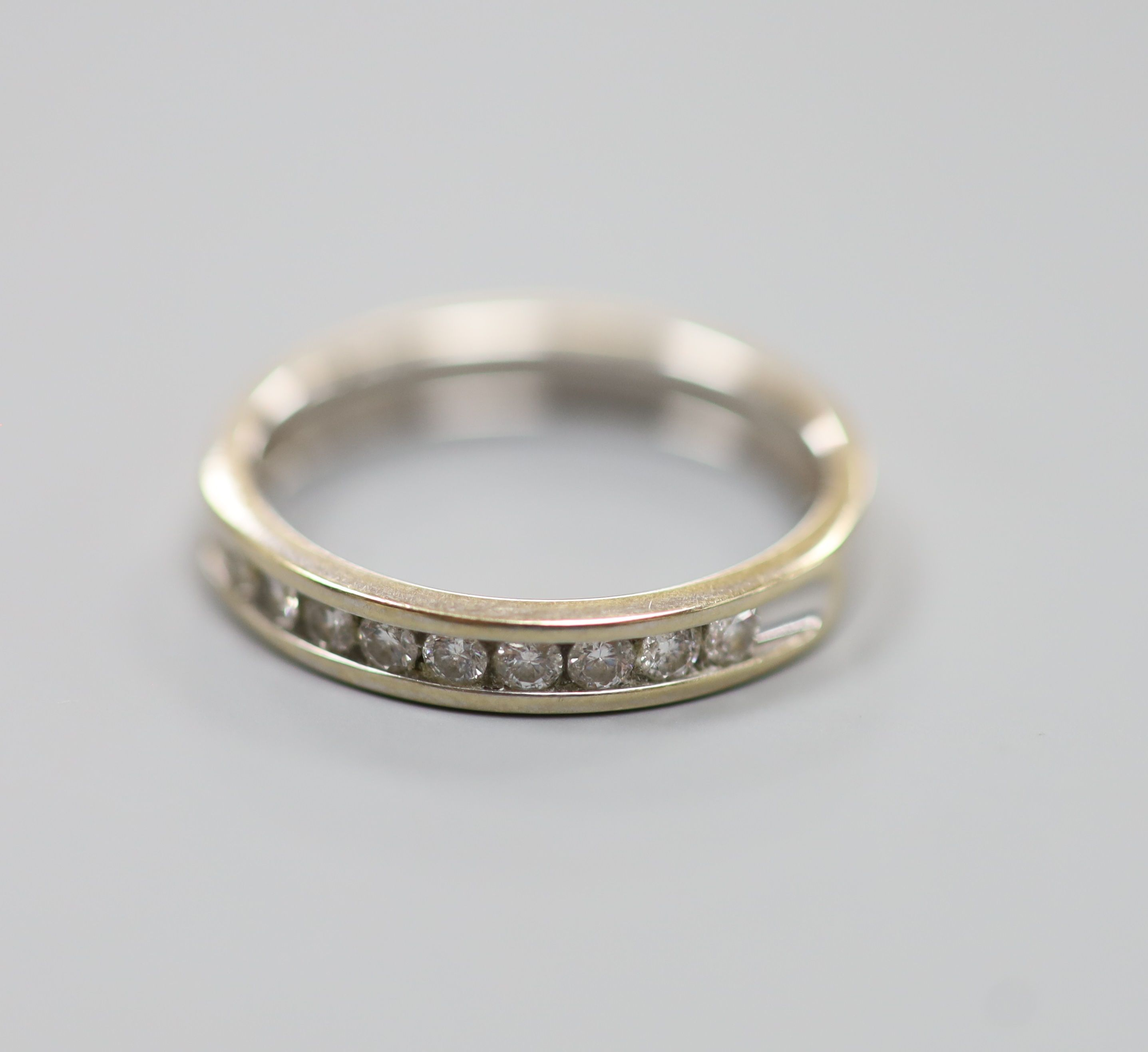 A modern 18ct white gold (worn) and nine stone channel set diamond half eternity ring, size P,gross