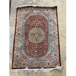A Persian part red ground silk multi-floral patterned rug, 110 x 80cm