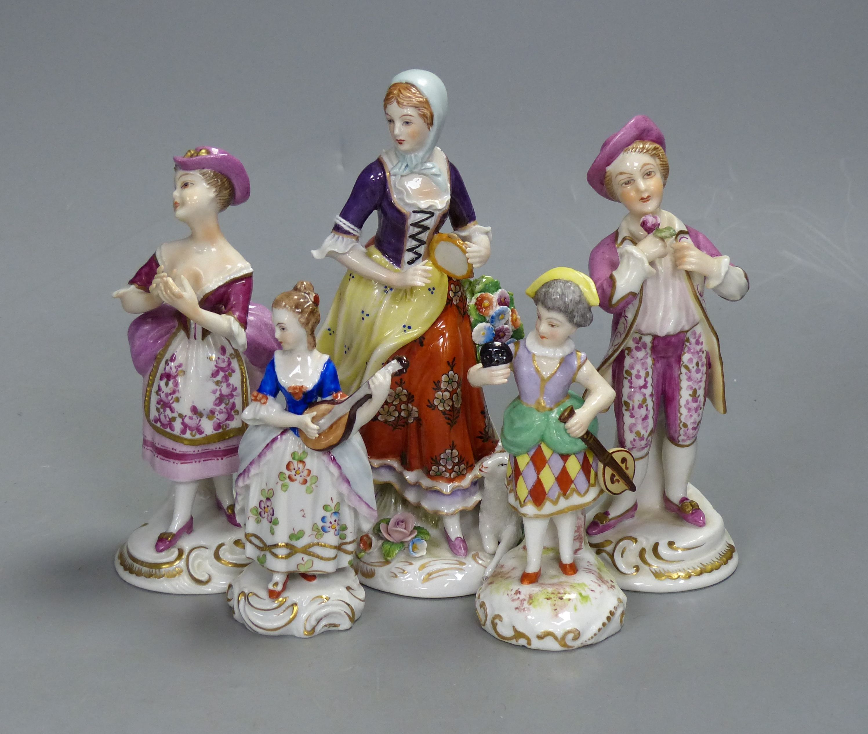 A German porcelain figure of a masked harlequin with stringed instrument and four other Continental