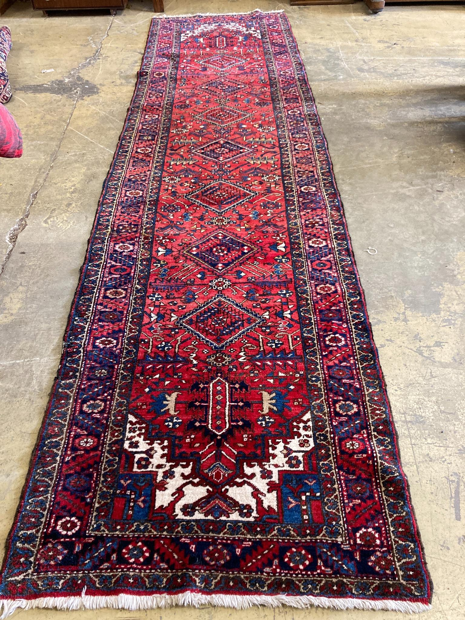 A North West Persian red ground hall carpet, 440 x 115cm
