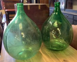 A pair of green glass carboys, height 64cm
