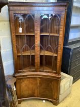A Georgian style mahogany floor-standing corner display cabinet,having concave front, fitted a pair