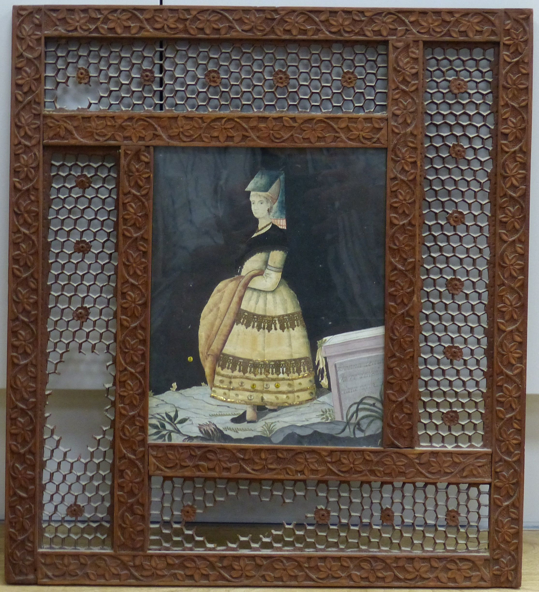 An early 19th century painted silk and gilt metal portraitdepicting a young woman wearing
