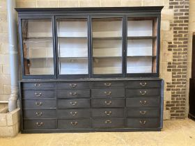 A Victorian painted pine glazed cabinet fitted twenty drawers, by repute The Bible Cabinet from