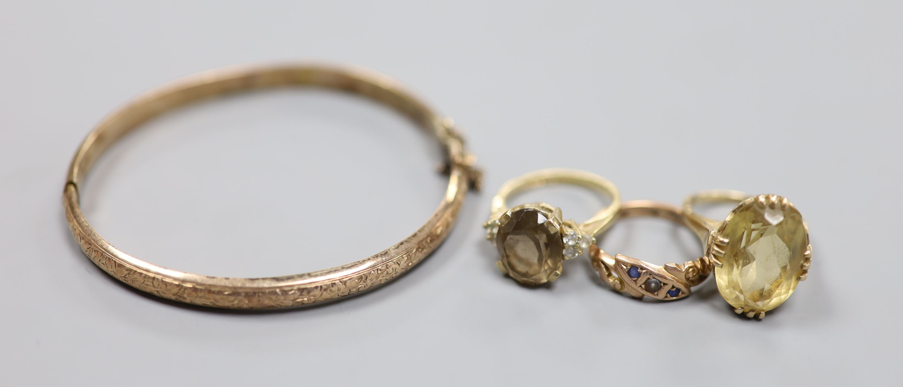 Three assorted 9ct and gem set rings and a 9ct gold hinged bangle,gross 18.1 grams.