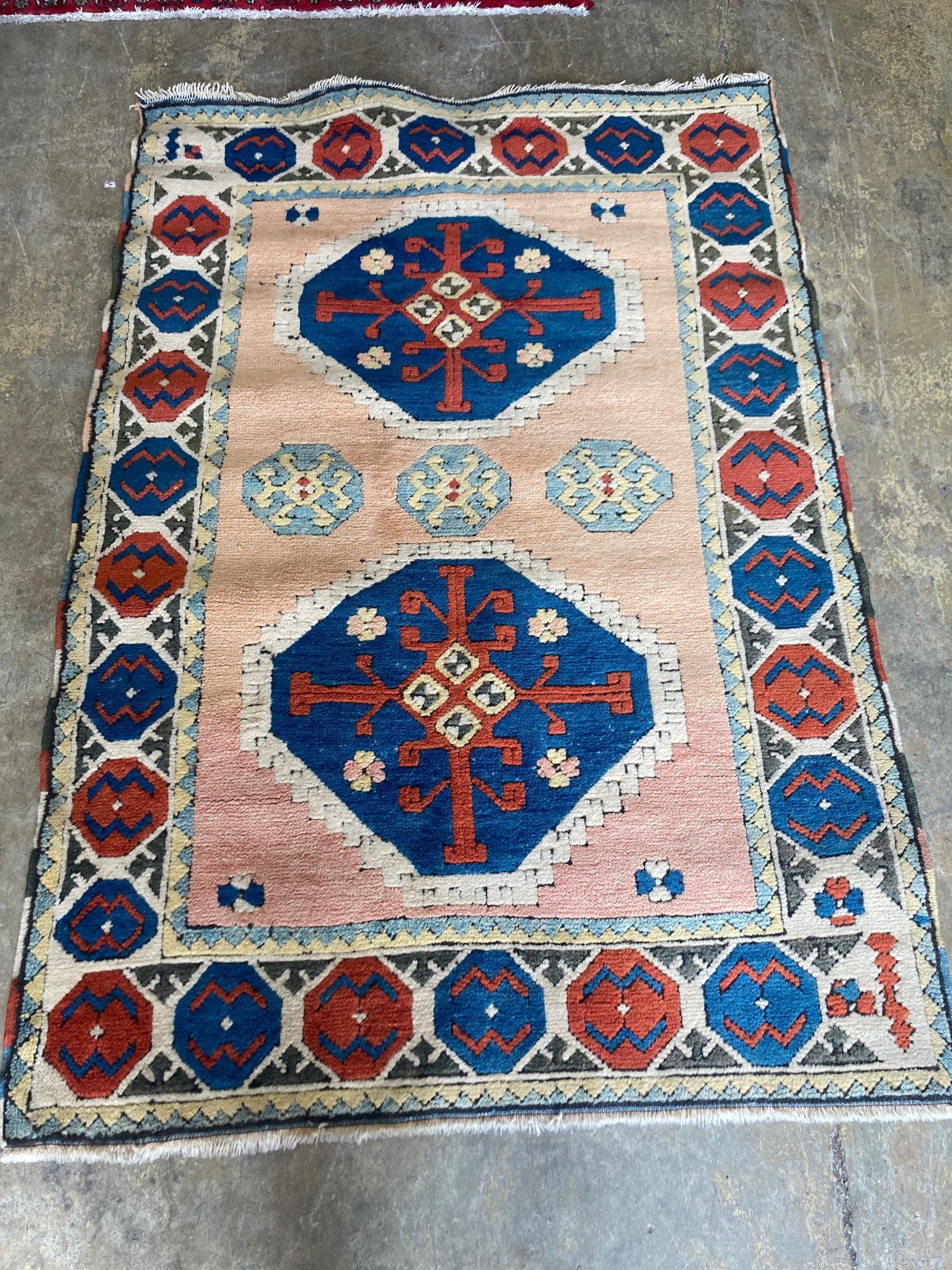 A Kazak style peach ground rug, 180 x 126cm
