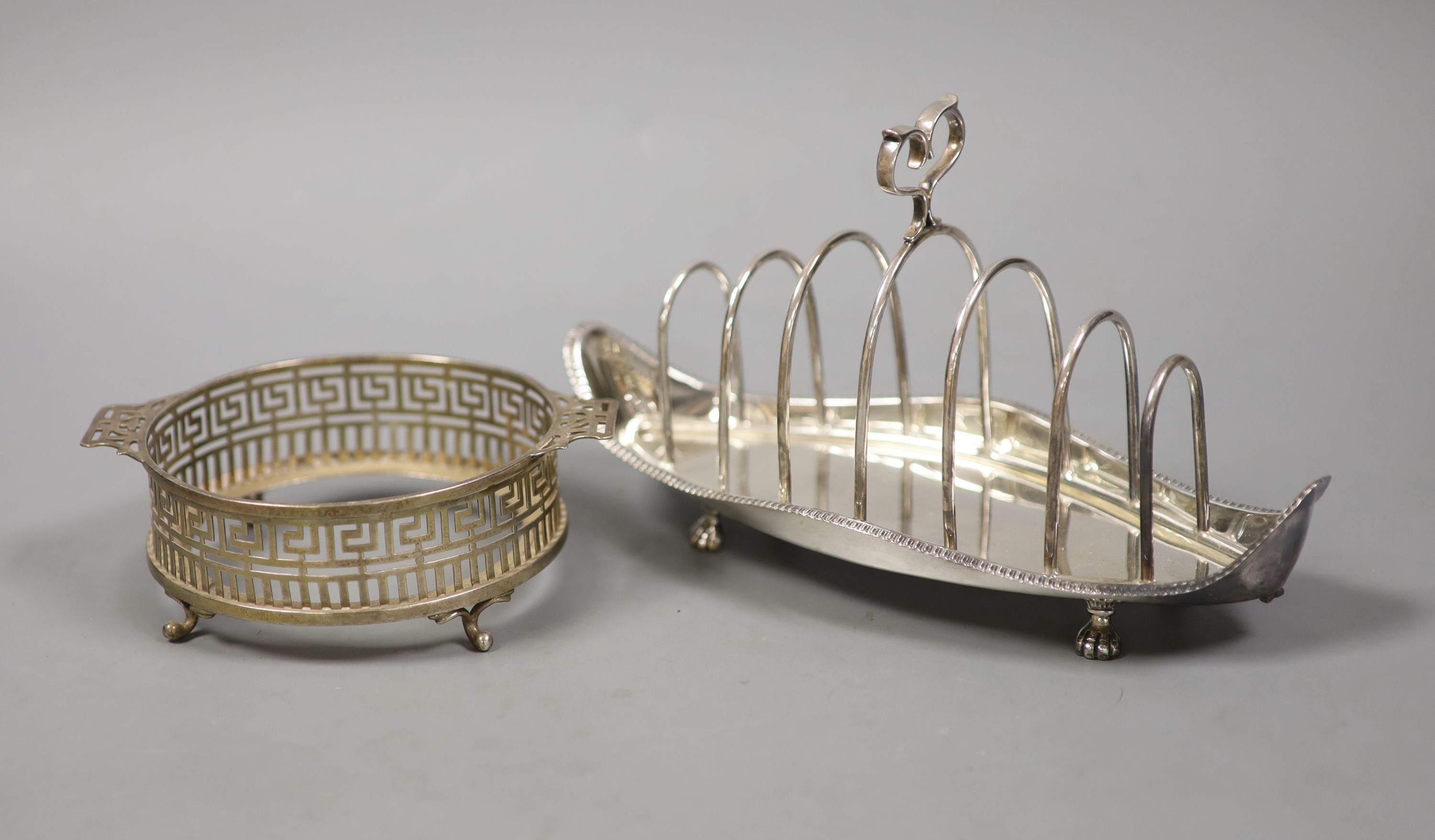 A late Victorian silver seven bar toastrack, with shaped ring handle, on paw feet, Josiah