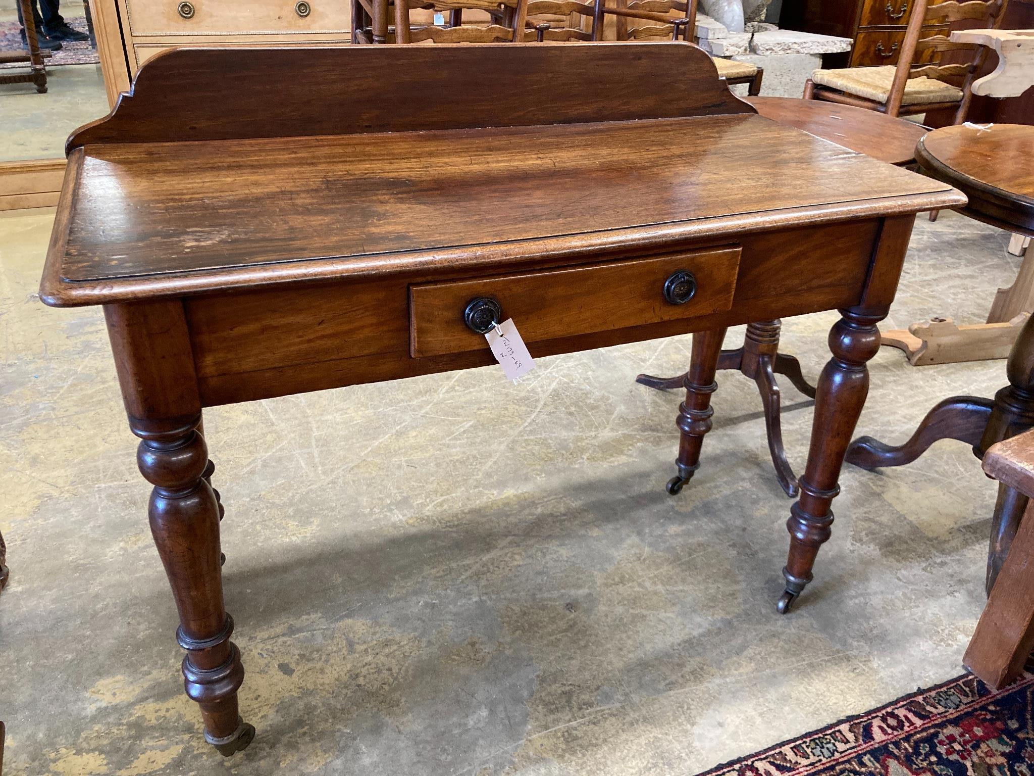 A Victorian mahogany writing tablefitted two small drawers on turned tapered legs, length 106cm,
