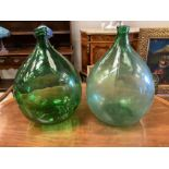 A pair of green glass carboys, height 62cm
