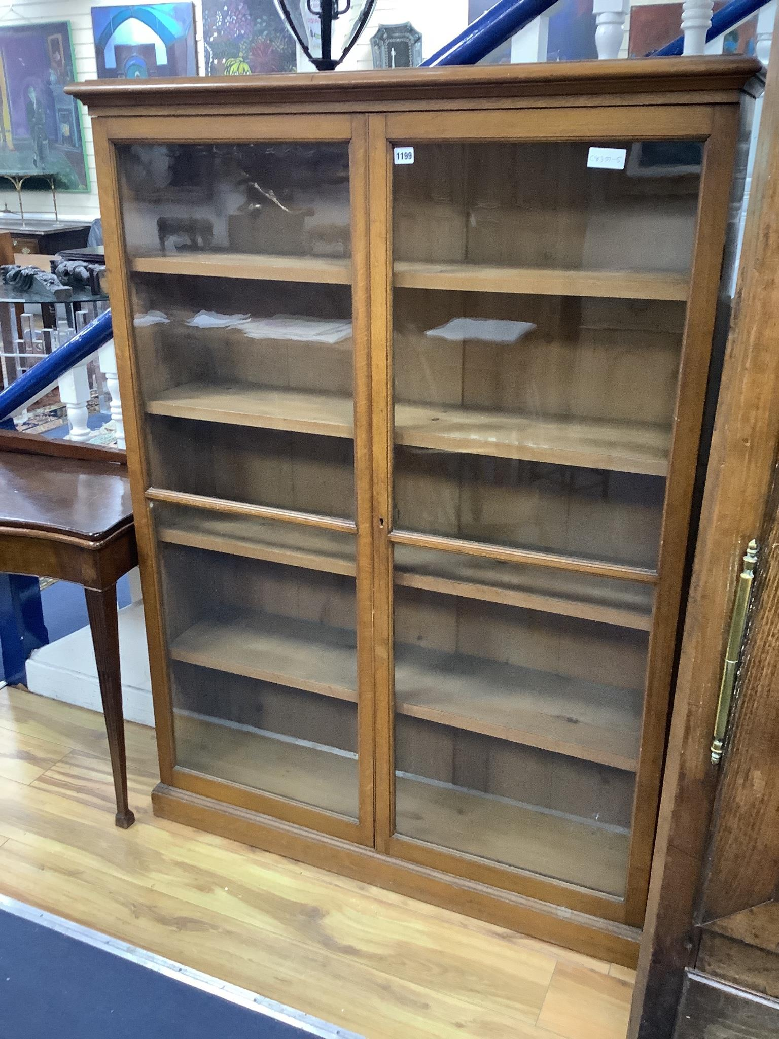 A late Victorian oak two door glazed bookcase, width 112cm, depth 29cm, height 152cm