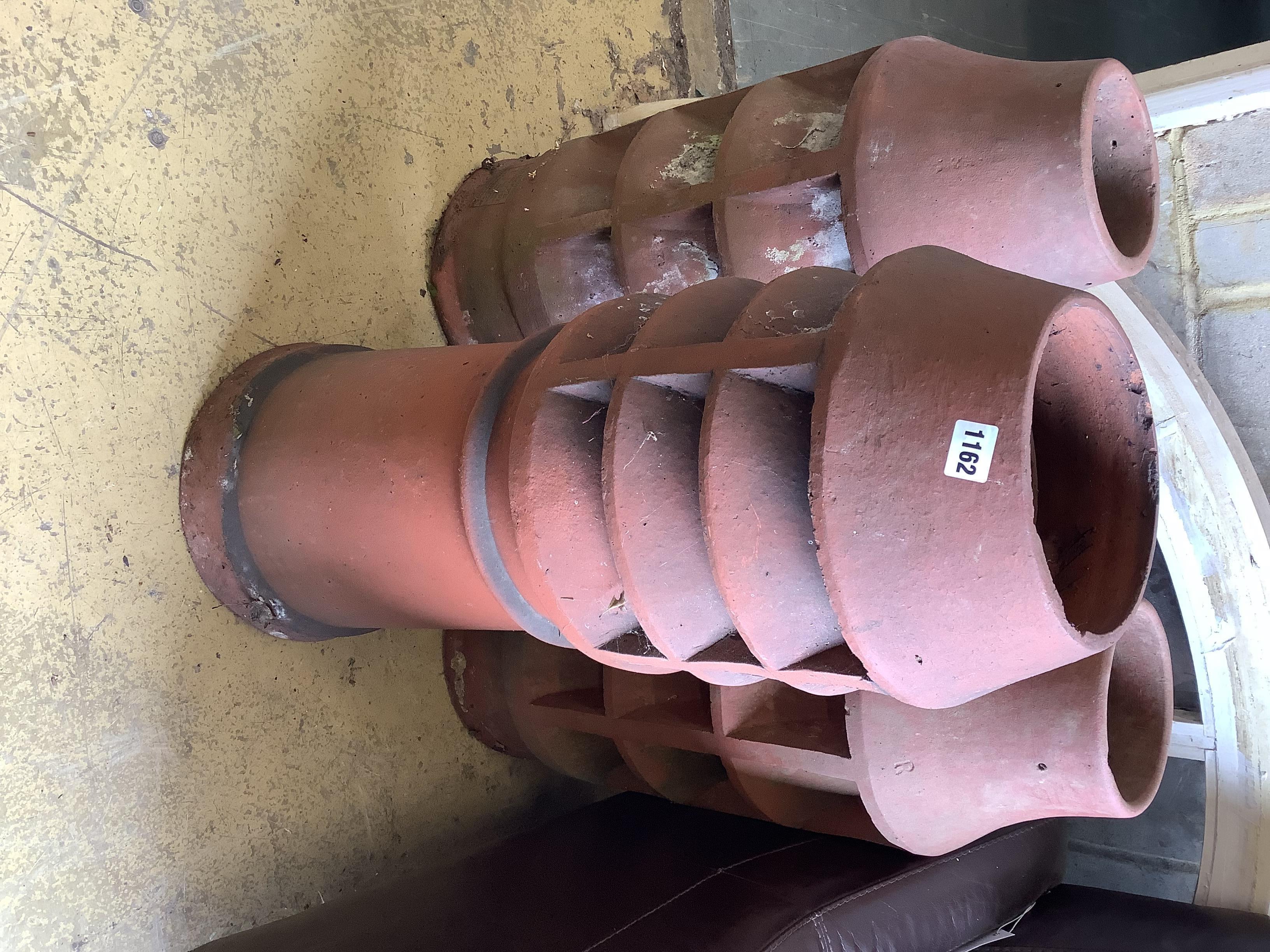 Three vintage terracotta chimney pots, largest 84cm high