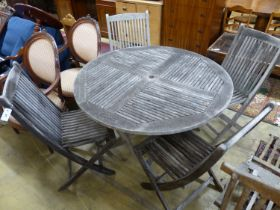 A teak garden table, 125cm diameter and four matching chairs, all folding
