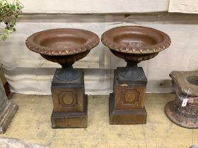 A pair of glazed stoneward garden urns on pedestals, height 79cm, diameter 51cm