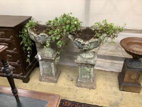 A pair of reconstituted stone garden urns on pedestals, height 97cm, width 55cm