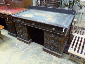 A late Victorian carved oak pedestal desk, length 138cm
