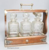 An oak three decanter tantalus, with key