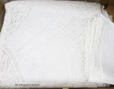 A finely worded tapelace and cutwork white tablecloth with matching serviettes and a similar ecru