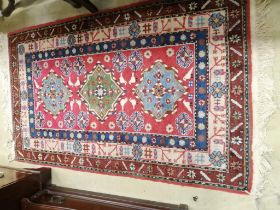 A Caucasian style red ground rug, 155 x 92cm