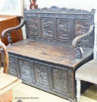 A late 19th century Flemish carved oak box seat settle, W.140cm D.62cm H.105cm
