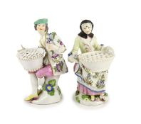 A pair of Meissen figural flower holders c.1755,modelled as a seated lady and gentlemen holding a