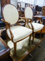 A pair of upholstered elbow chairs, width 57cm, height 100cm