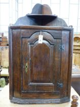 A late 17th century oak hanging corner cupboard,having shelved superstructure over an arched