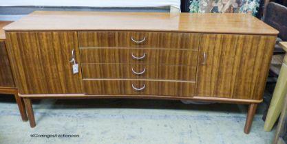 A Gordon Russell Ltd teak and Indian Laurel concave sideboard Model R810 circa 1960, length 183cm,