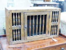 A 17th century style oak hanging food cupboard,with spindle front and door, width 69cm, depth 25cm,