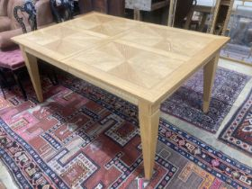 A contemporary inlaid oak extending dining table, 236cm extended, two spare leaves, W.106cm H.75cm
