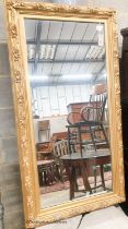 A rectangular carved giltwood framed wall mirror, width 67cm, height 132cm